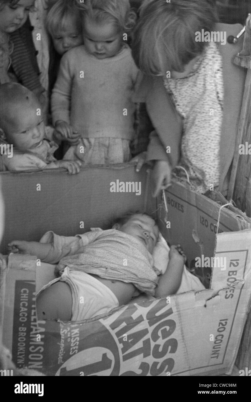 Baby in a cardboard box crib at a Kern California migrant camp pre-school while mother works in the fields. Nov. - Stock Image