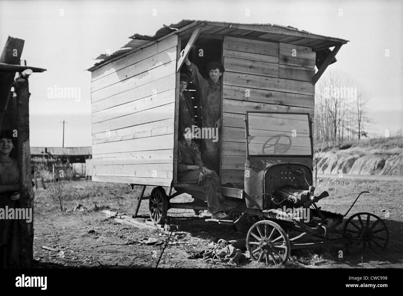 Three men stand in the entry of their shack home built on an old truck chassis. Between Camden and Bruceton Tennessee. - Stock Image