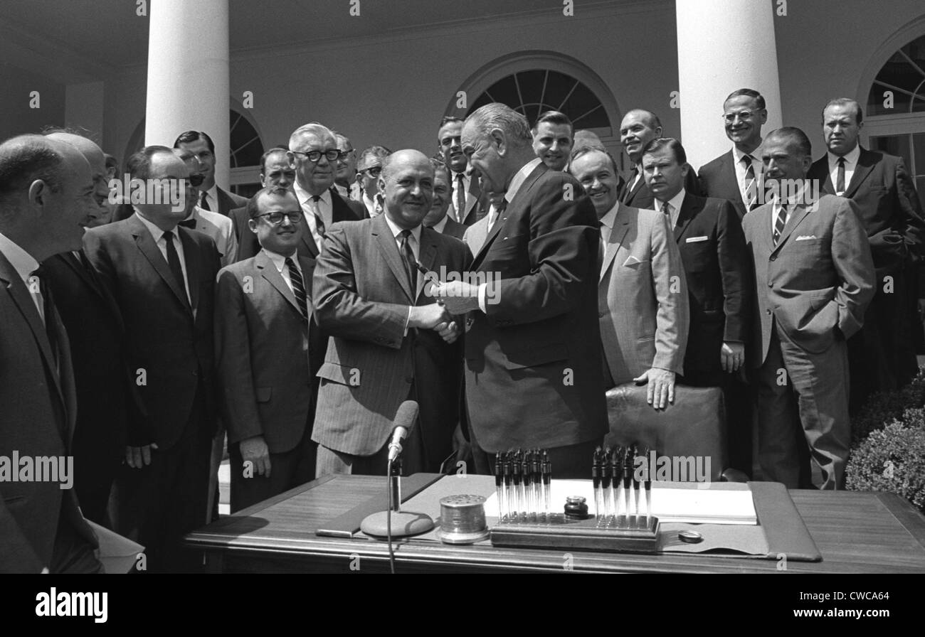 LBJ's Great Society programs. President Lyndon Johnson shakes HUD Secretary, Robert Weaver, after signing of the Stock Photo