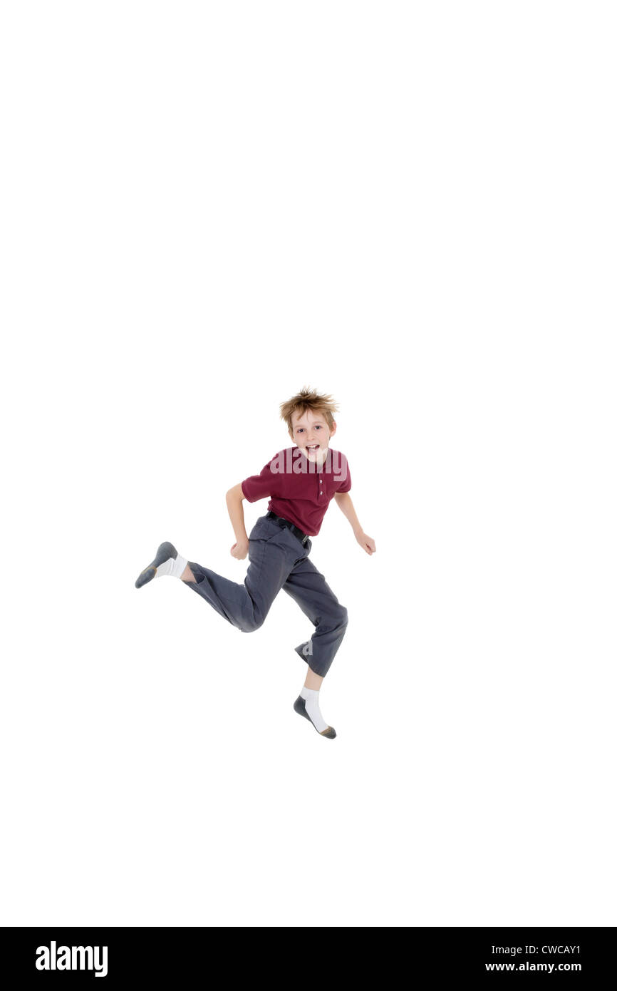 Portrait of cheerful pre-teen boy jumping over white background - Stock Image