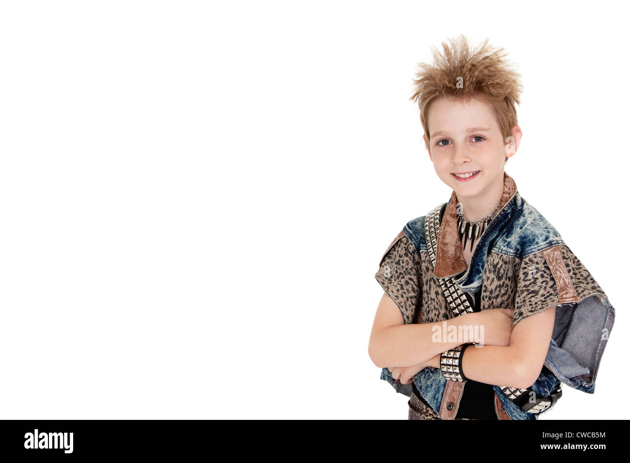 Portrait of pre-teen boy standing with arms crossed over white background - Stock Image