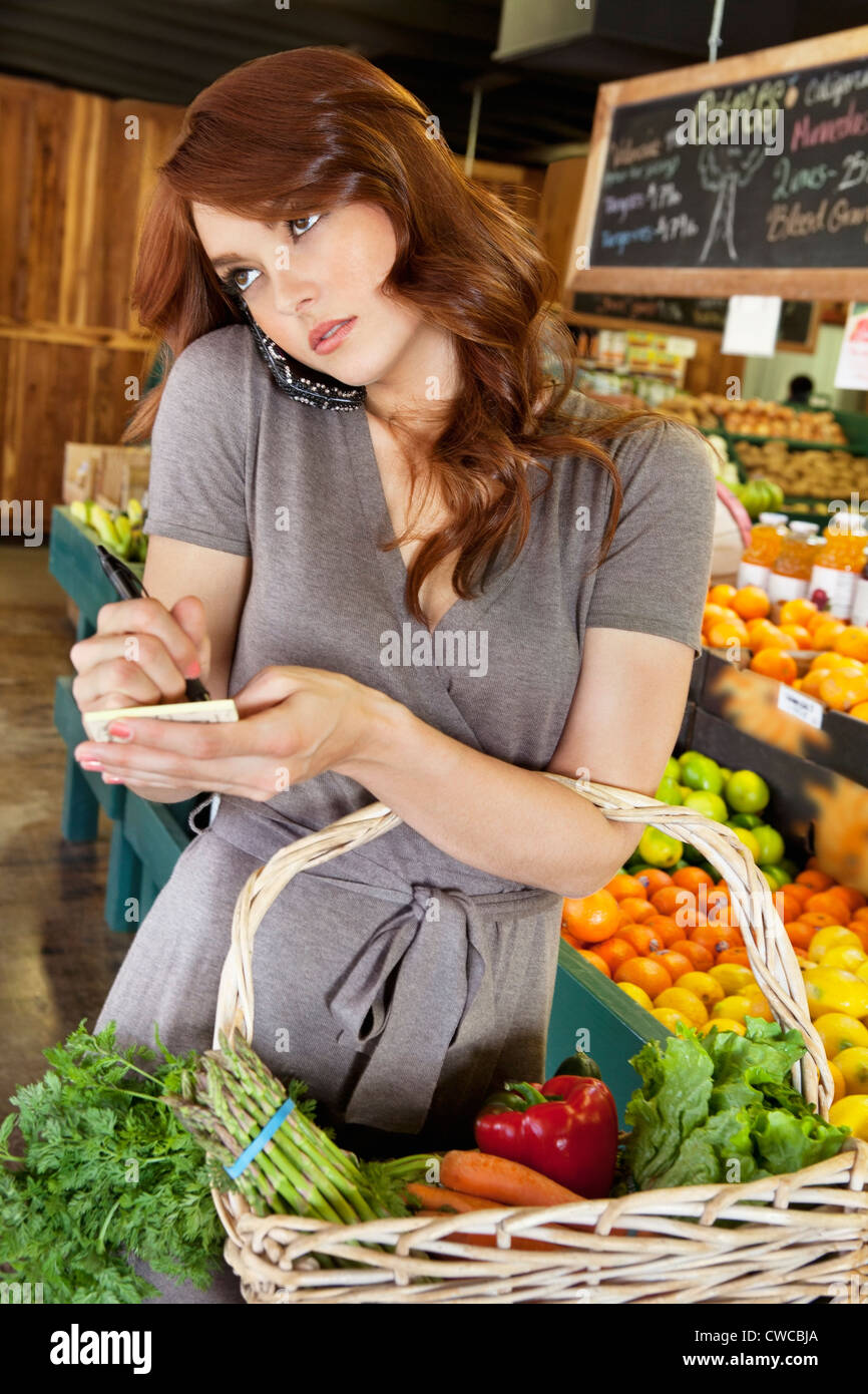 beautiful young woman listening to mobile phone while making a note of shopping list in market