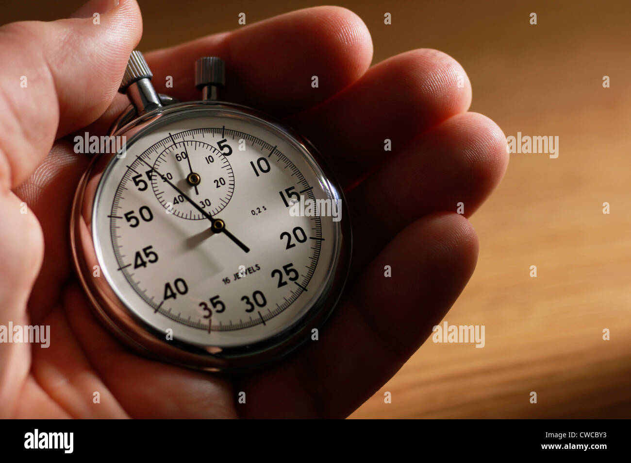Man holding stopwatch - Stock Image