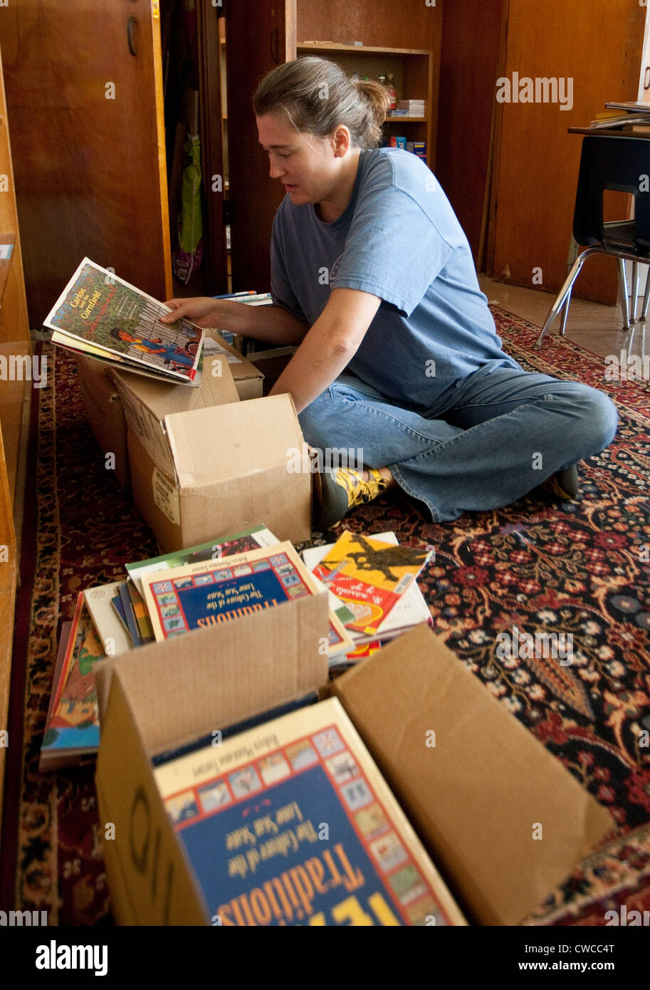 White female volunteer helps organize books to be used in classroom of elementary school in Austin, Texas - Stock Image