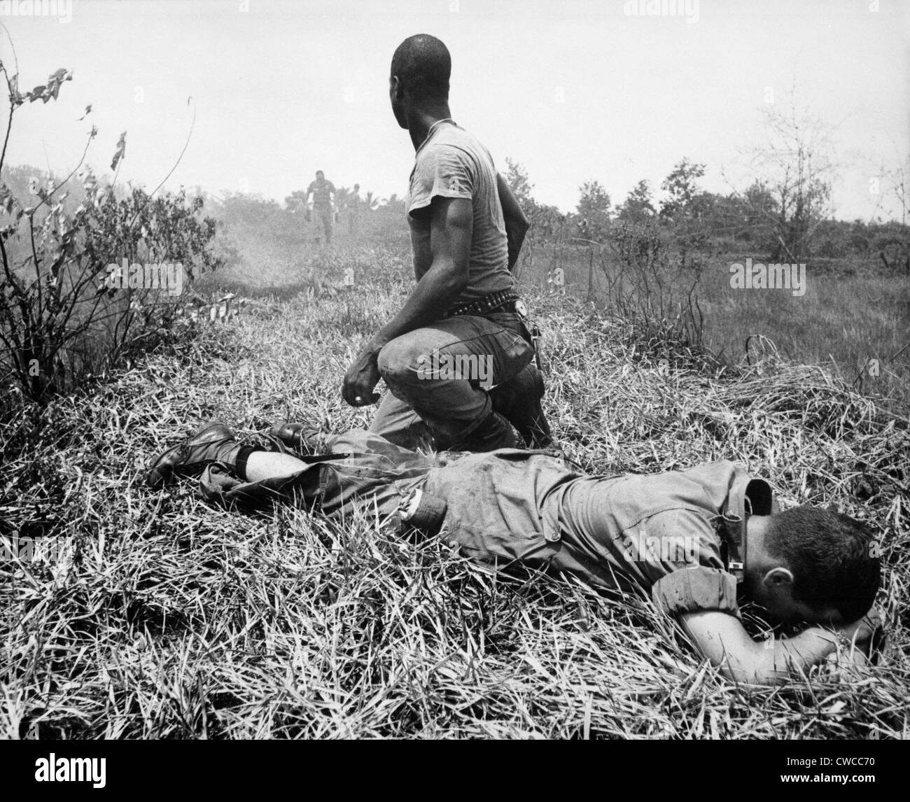 Vietnam War. An African American Infantry medic treats a lieutenant's leg, that was burned by an exploding Viet - Stock Image