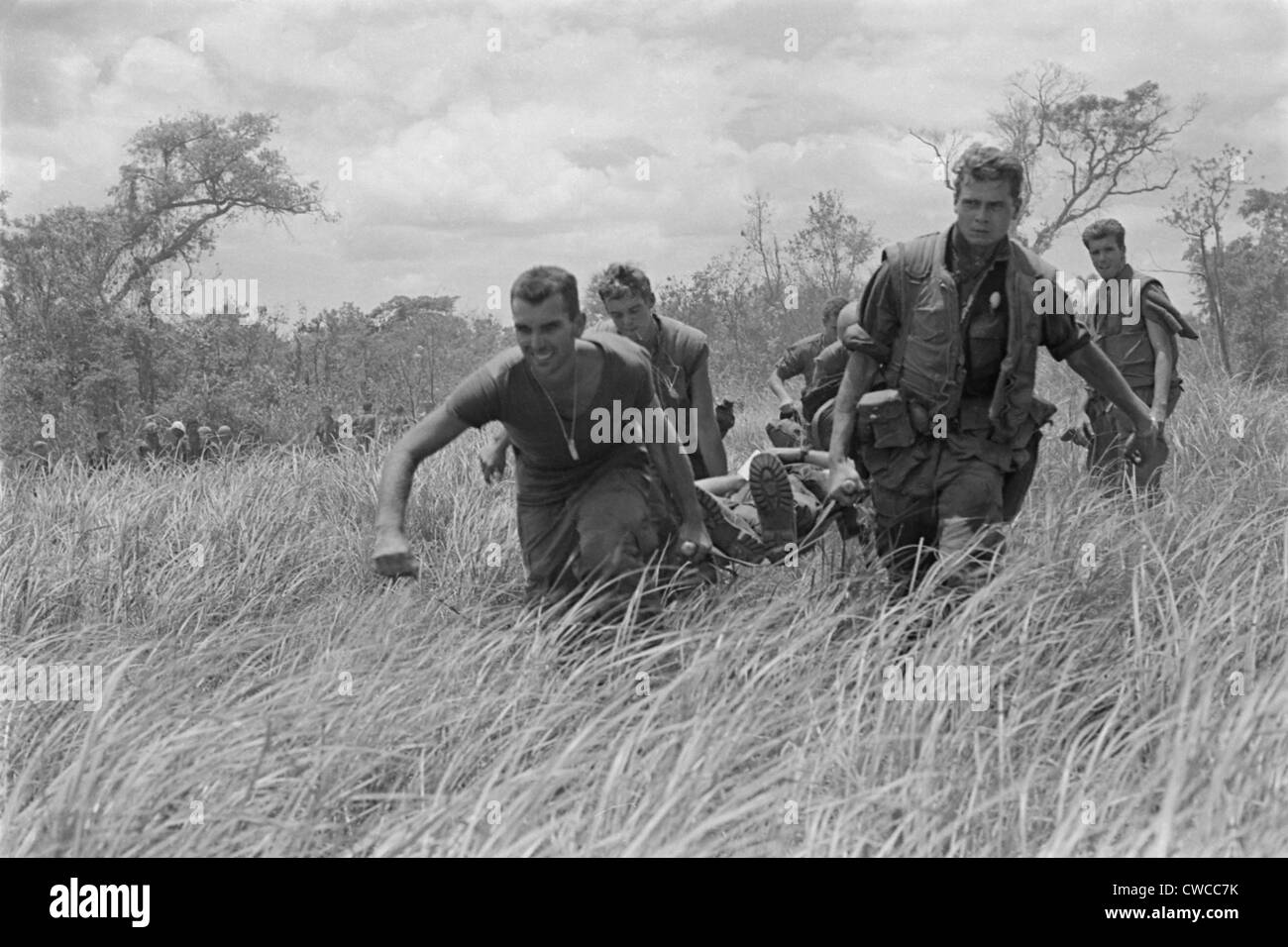 Vietnam War. While under heavy fire, US Marines are carry a wounded Marine to the evacuation helicopter near the - Stock Image