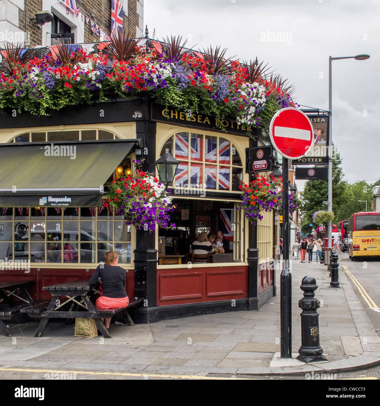 Colourful flags and floral displays decorate the Chelsea Potter pub at the time of the London 2012 Olympic games - Stock Image