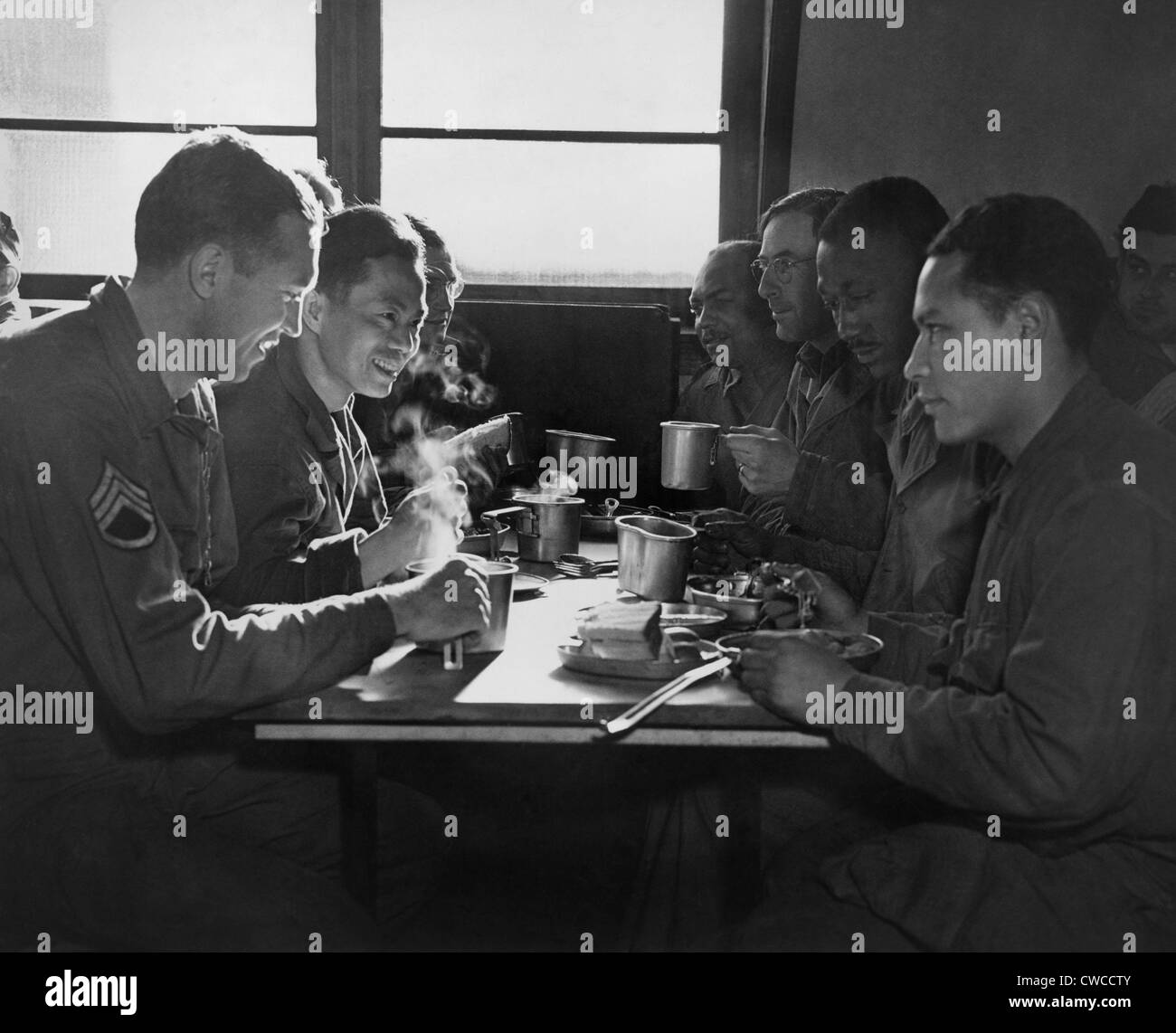 African American, Chinese, Puerto Rican, and White US soldiers eating together in a mess hall. They are all serving - Stock Image