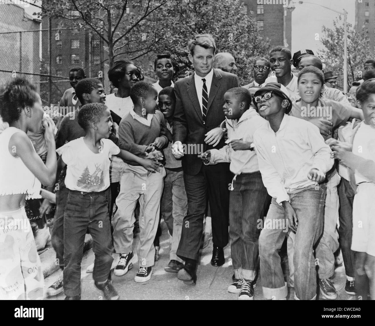 Attorney General Robert Kennedy surrounded by African American children. He was visiting a summer reading program - Stock Image