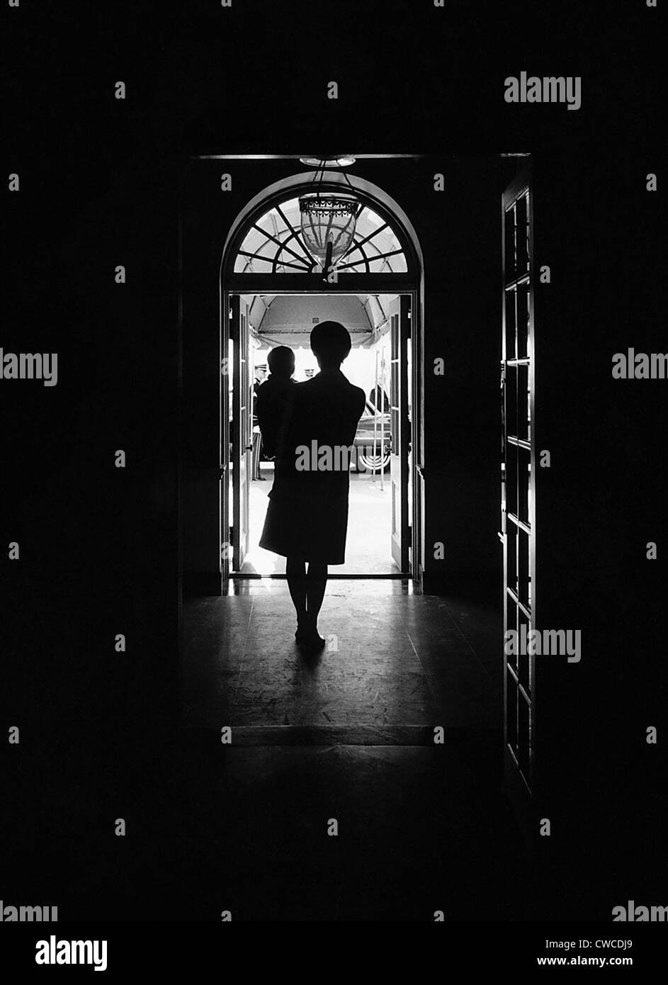 Silhouette portrait of Jacqueline Kennedy carrying her one year old son John Kennedy Jr. in the White House, South - Stock Image