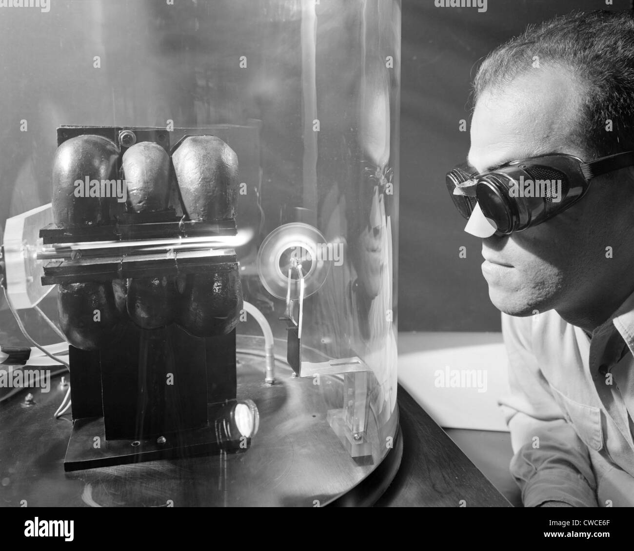 Scientist with protective glasses and nose cover experimenting with Ion Jet rocket propulsion. Sept. 27, 1957. - Stock Image