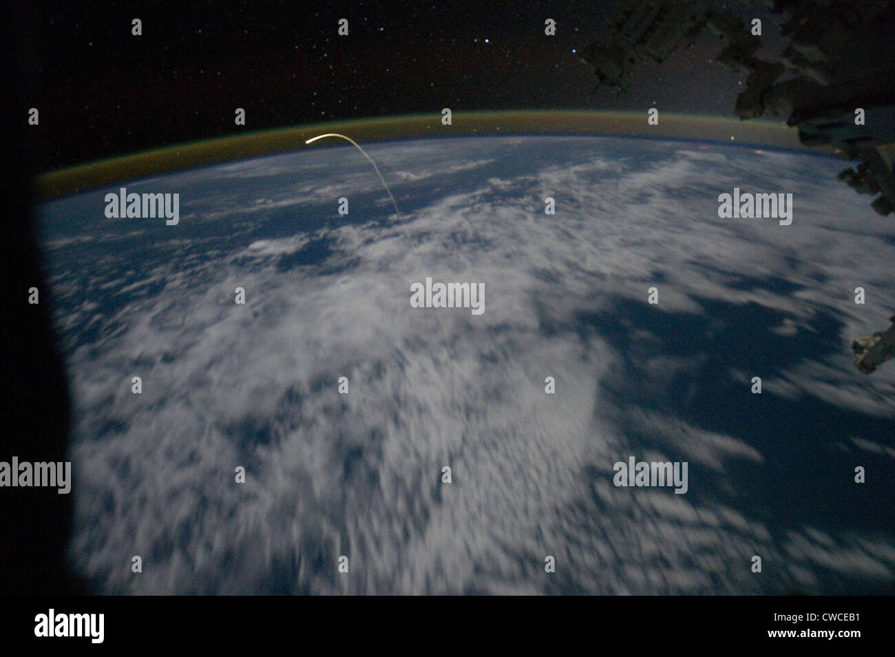 Space shuttle Atlantis re-entry flight path resembles a bean sprout against clouds and city lights. Photograph by - Stock Image