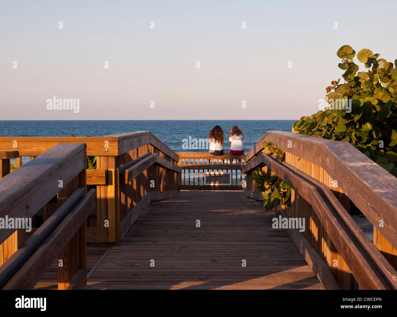 Two Girls Watching Sunset On Melbourne Beach In Brevard