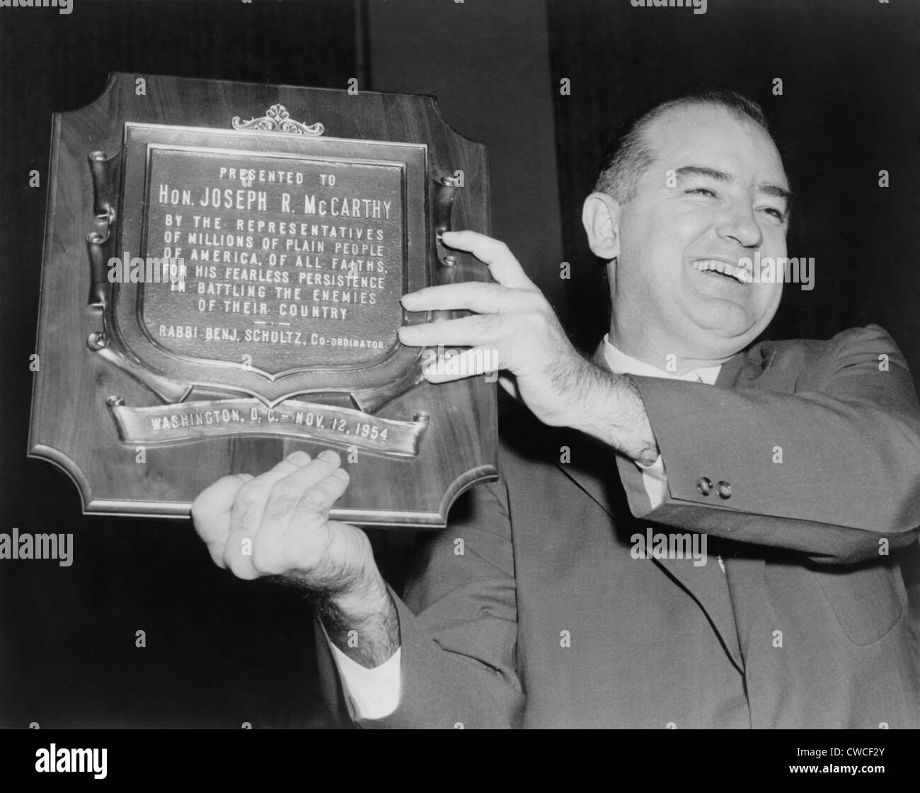 Wisconsin Senator Joseph McCarthy displays a plaque honoring him '…for his fearless persistence in battling - Stock Image
