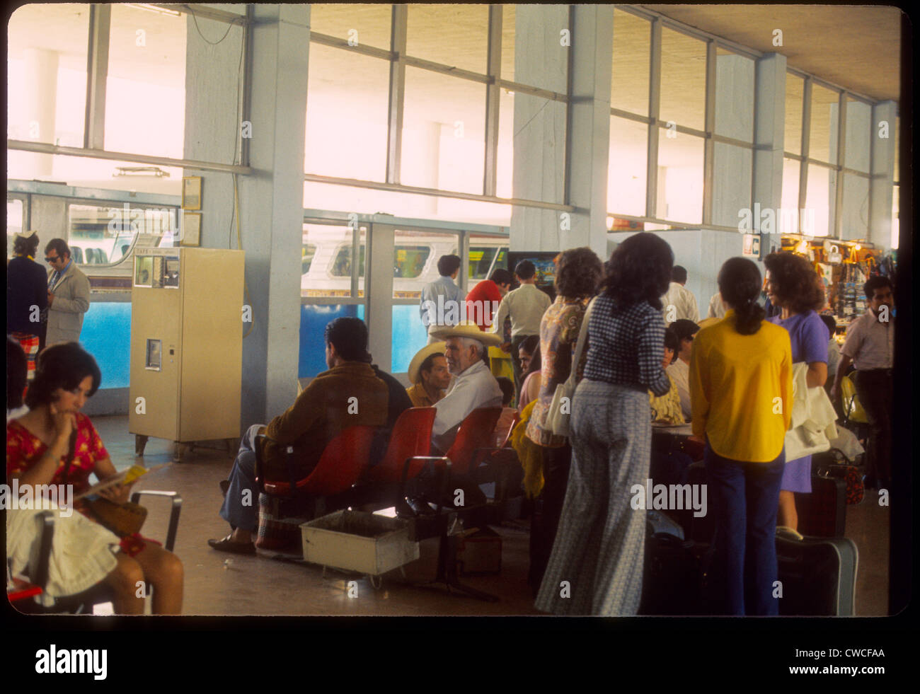 Mexicans waiting in bus station Guadalajara, Mexico 1973 1970s travel terminal fashion mexican day - Stock Image