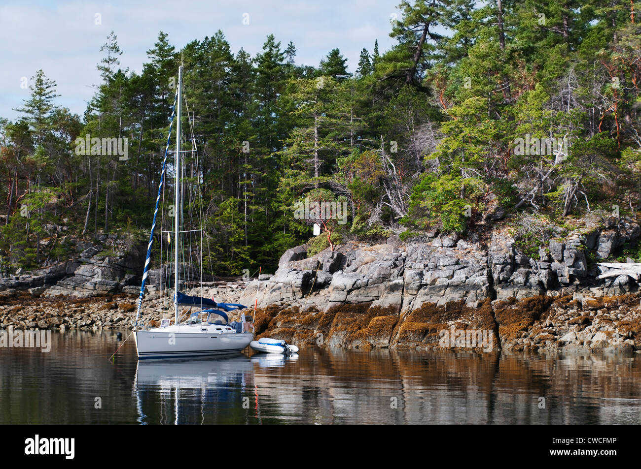 A sailboat is anchored along the shoreline of Mink Island in Canada's Desolation Sound on a beautiful sunny - Stock Image