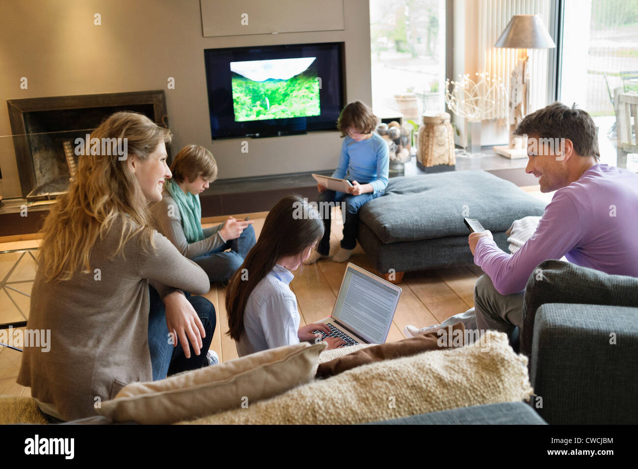 living room family family using electronic gadgets in a living room stock 11420