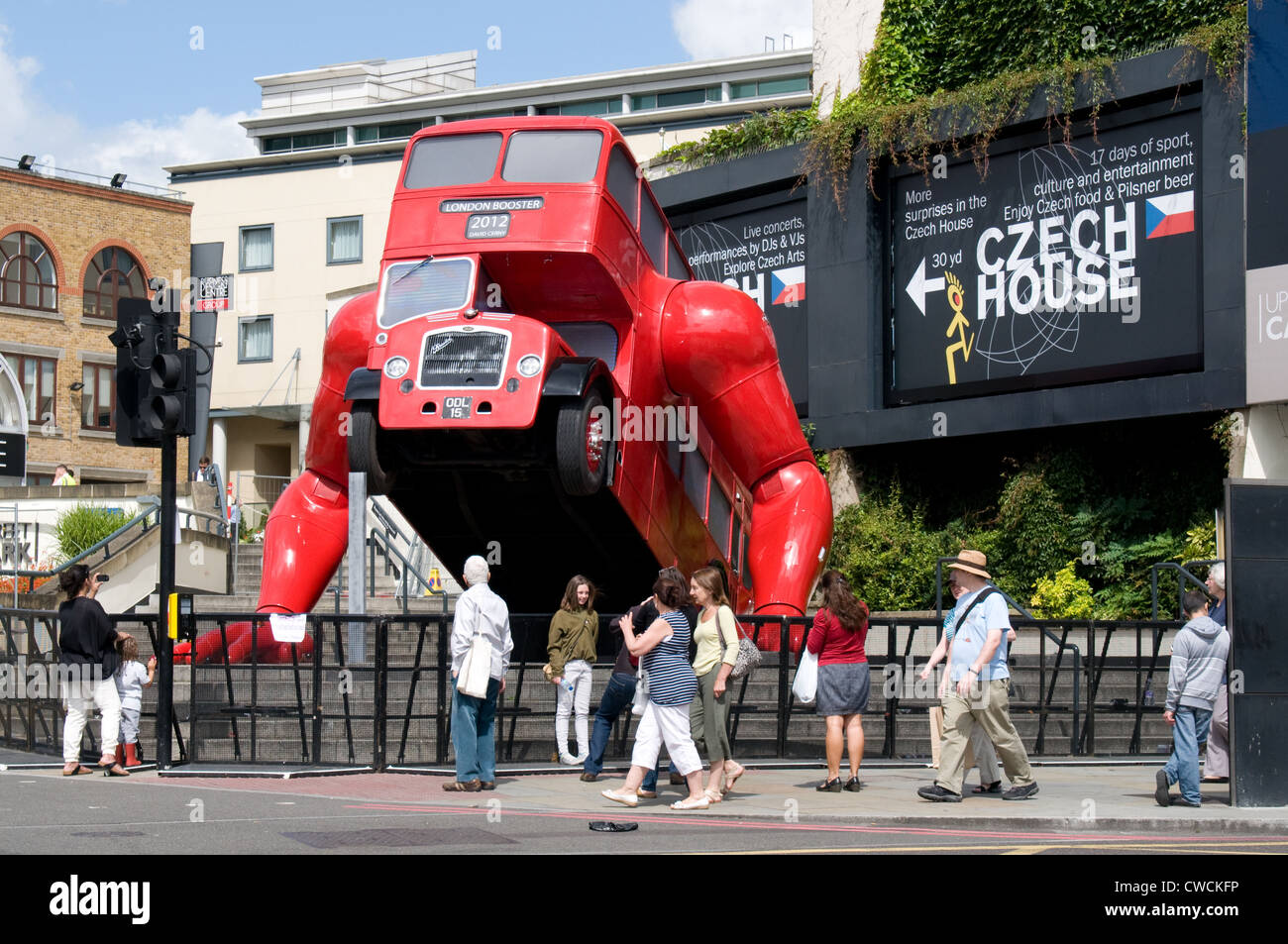 Visitors stand in front  of an old bus which has been converted into a work of art by Czech artist David Cerny. Stock Photo