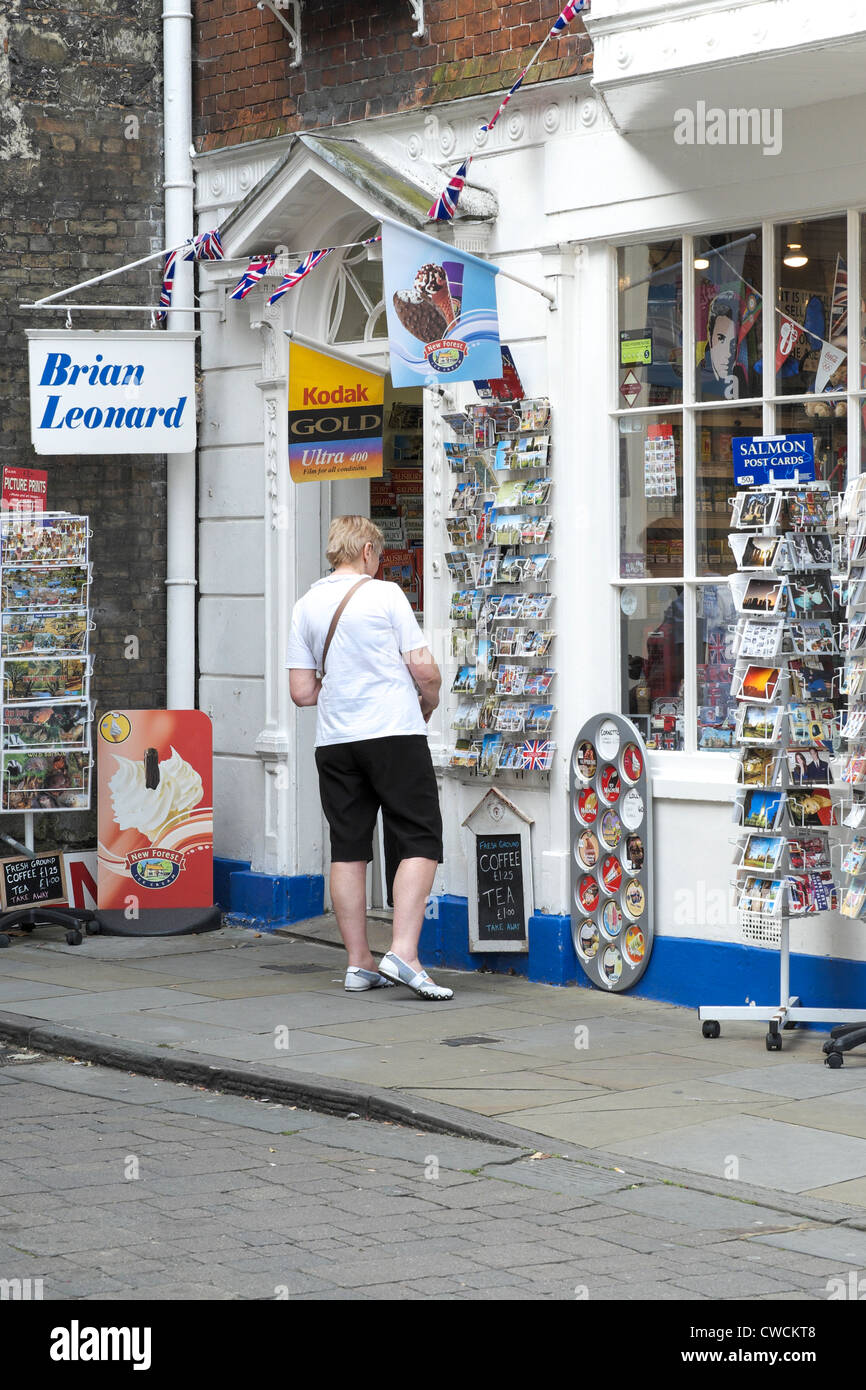 Lady studying picture postcards outside of a shop - Stock Image