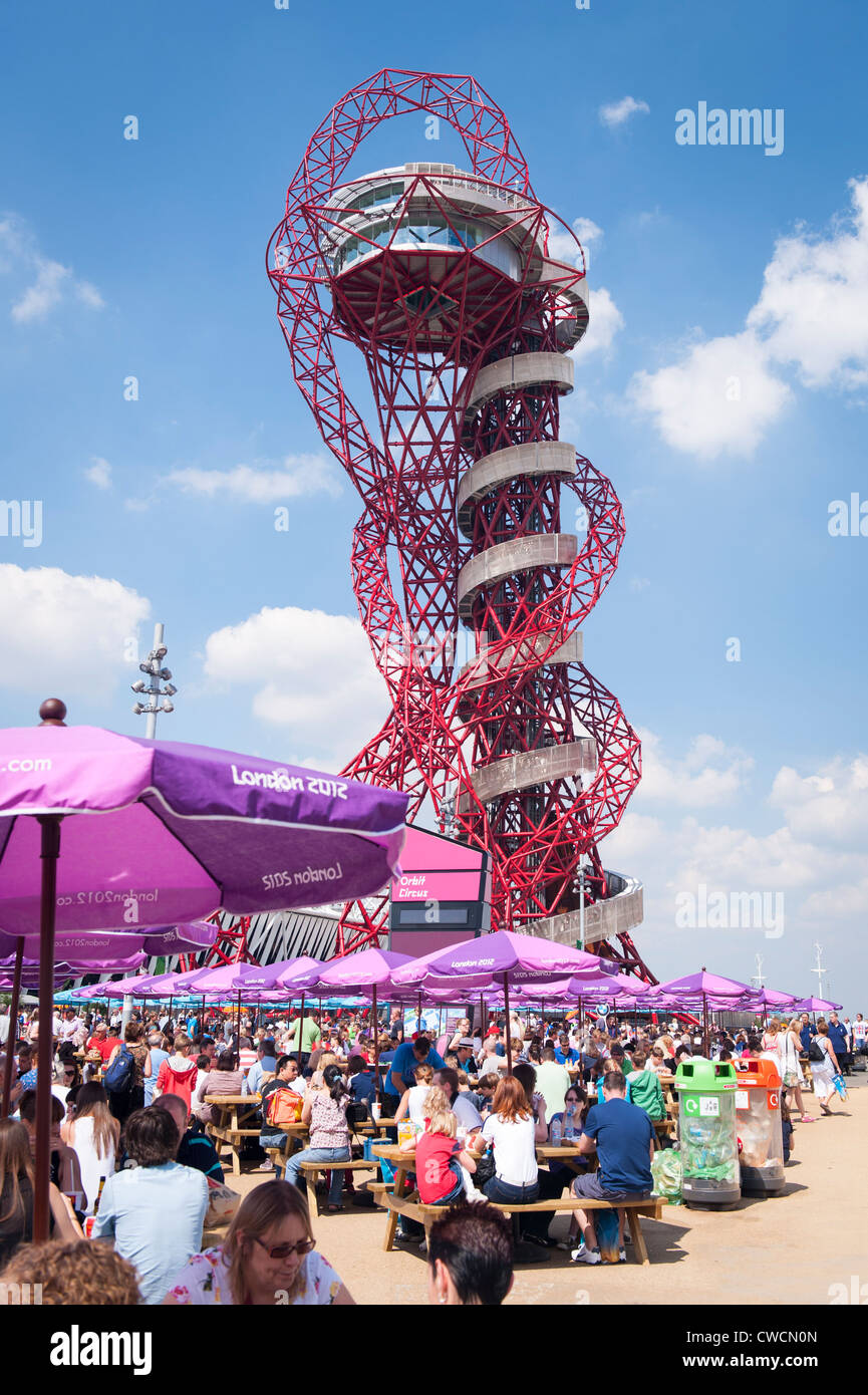 London 2012 Stratford Olympic Park the Anish Kapoor sculpture statue art work Orbit towers over crowds people 114 - Stock Image