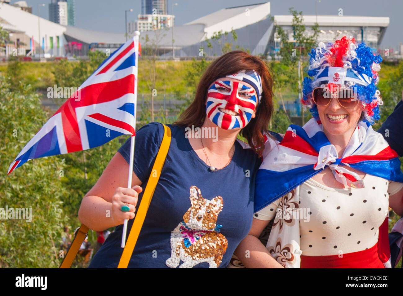 London 2012 , Stratford Olympic Park , revelers pretty young girls women females with Union Jack flag flags hat - Stock Image