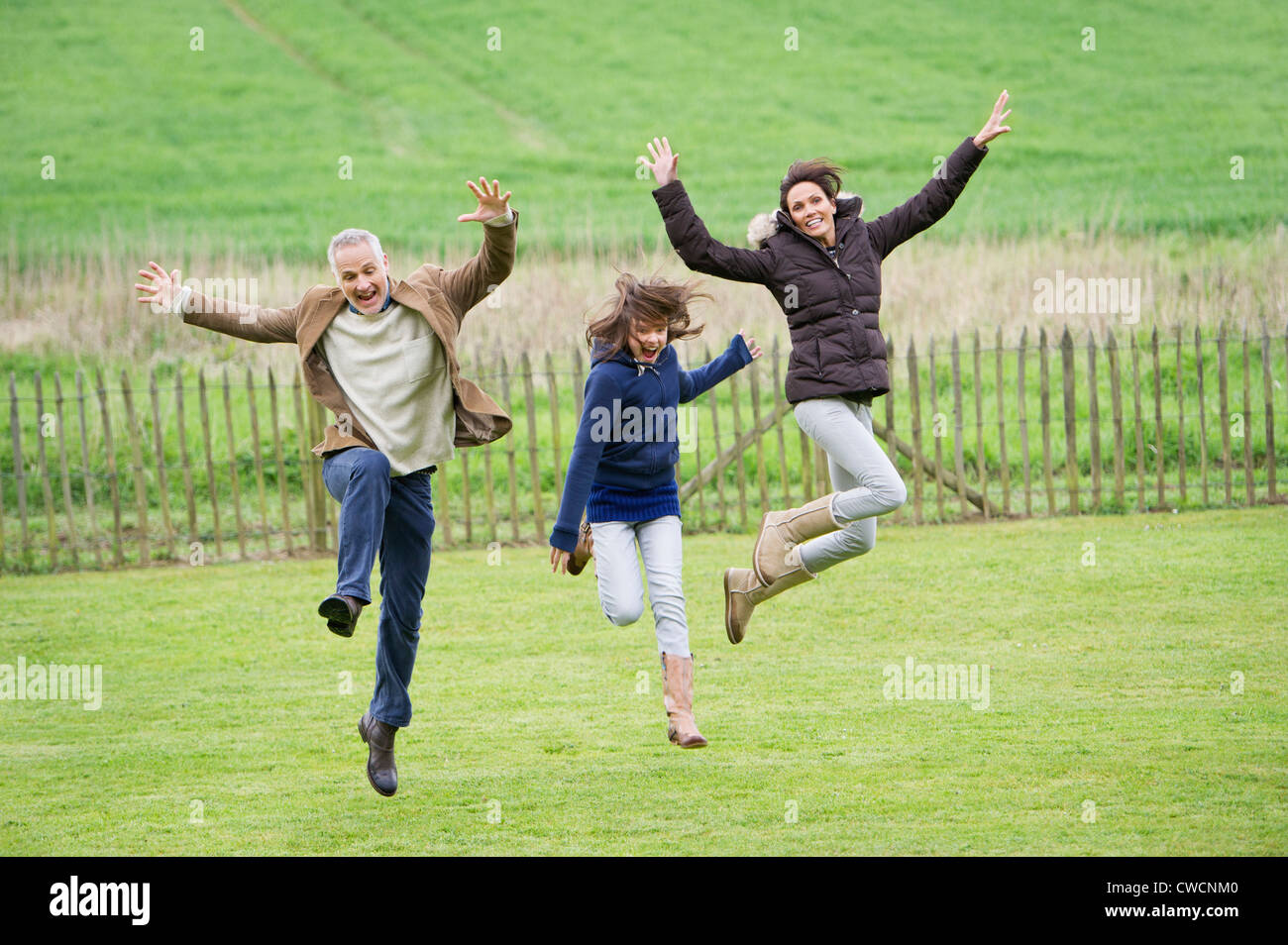 Happy family having fun in a field - Stock Image