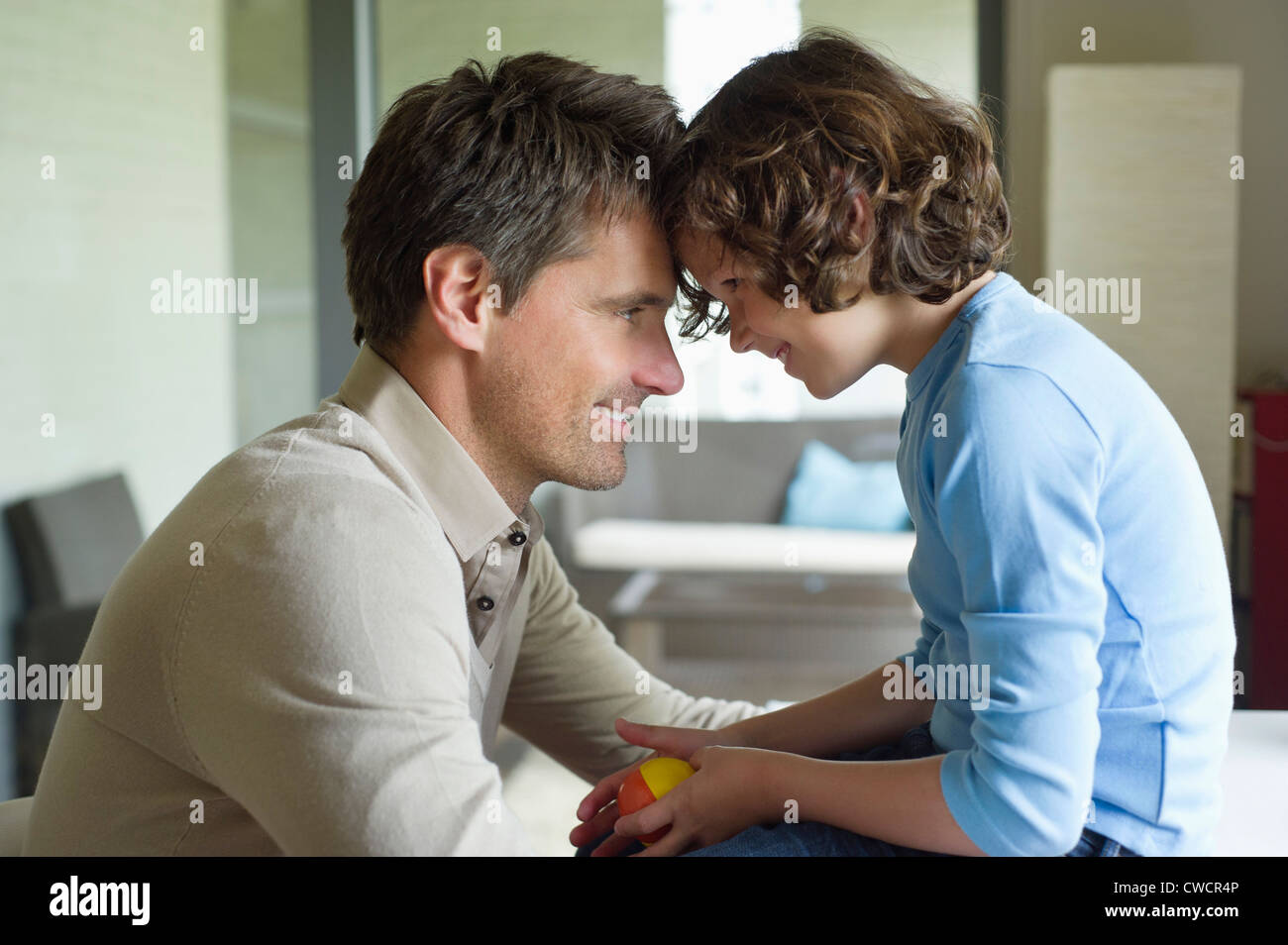 Man with his son face to face and smiling - Stock Image