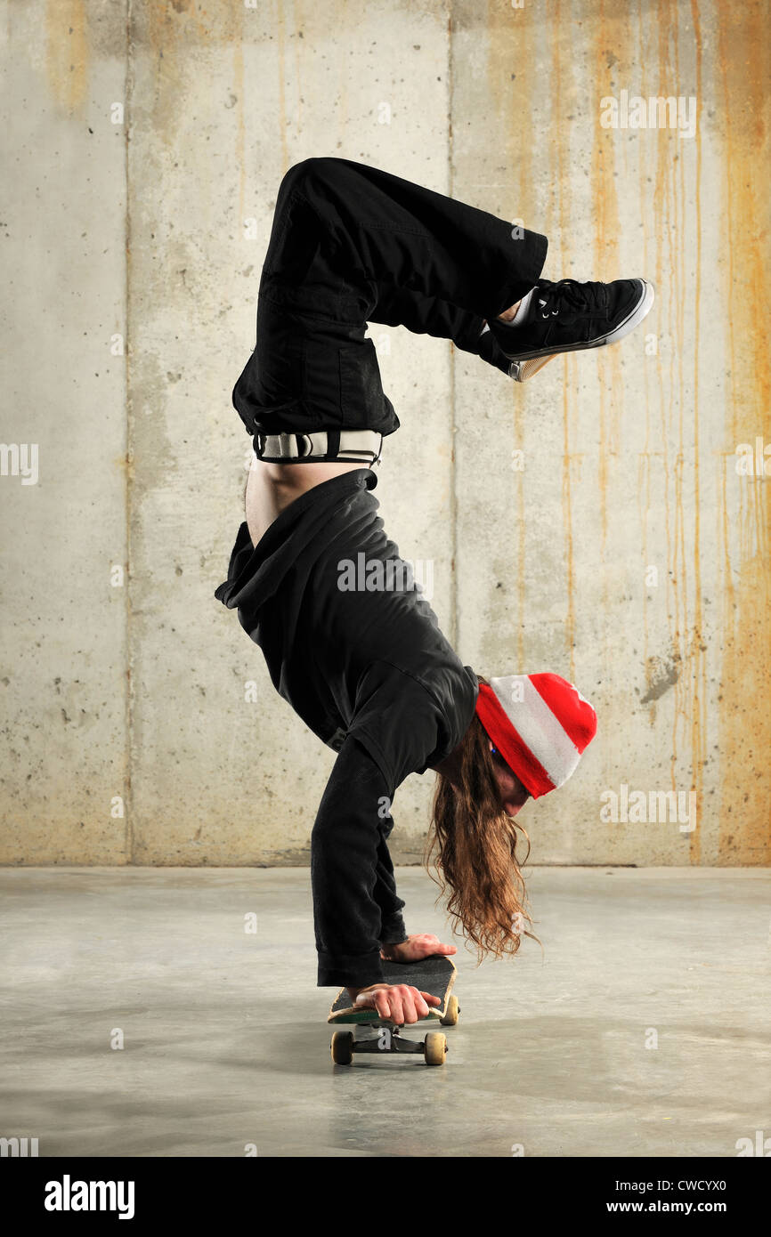 Young man doing handstand on skate board - Stock Image