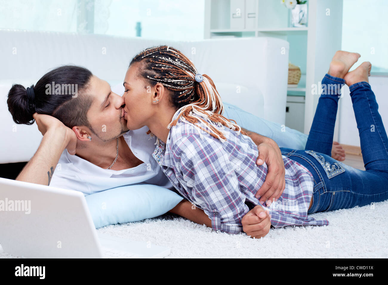 Image of young guy and his girlfriend having nice time at home - Stock Image