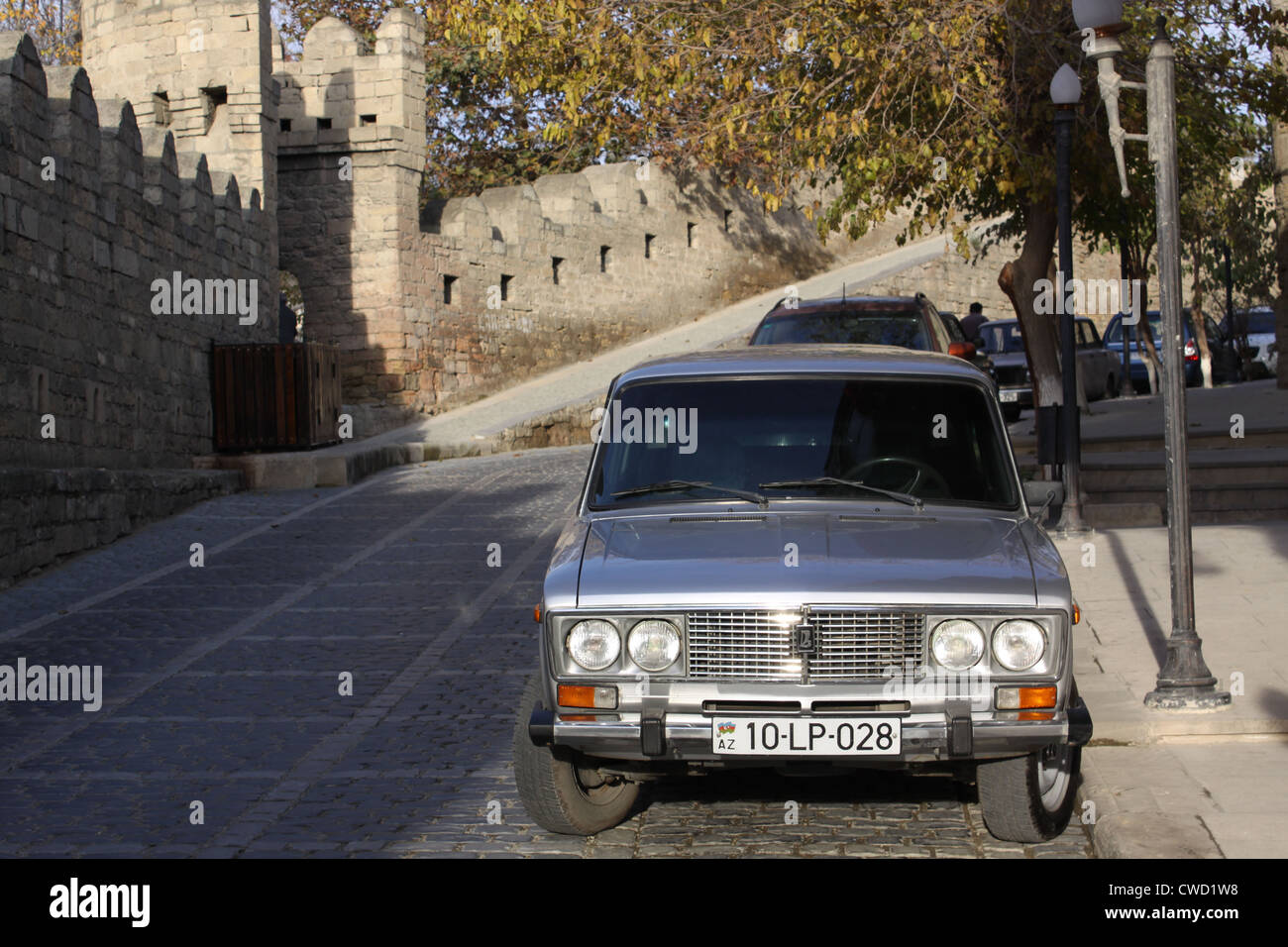 Baku, Azerbaijan. A street in the old town. A fragment of the fortress walls and retrocar - Stock Image