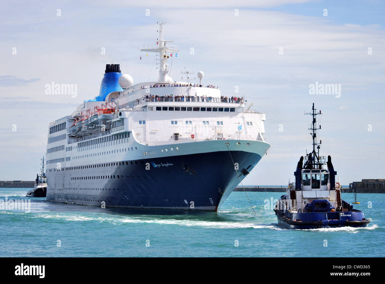 The cruise ship Saga Sapphire arrives in Dover during the day and is assisted past the Prince of Wales pier by the - Stock Image