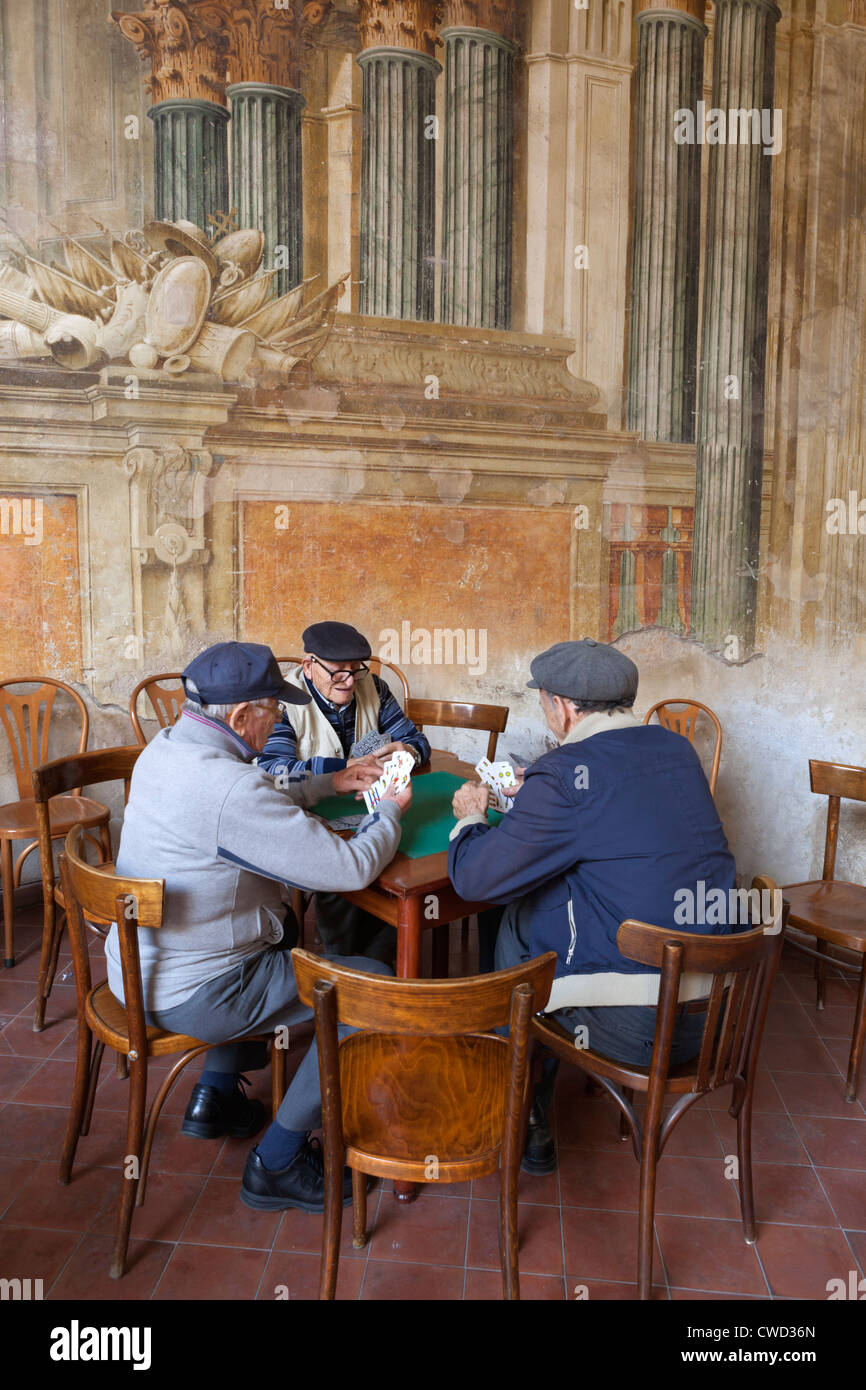 Elderly locals playing cards off Via San Cesareo - Stock Image