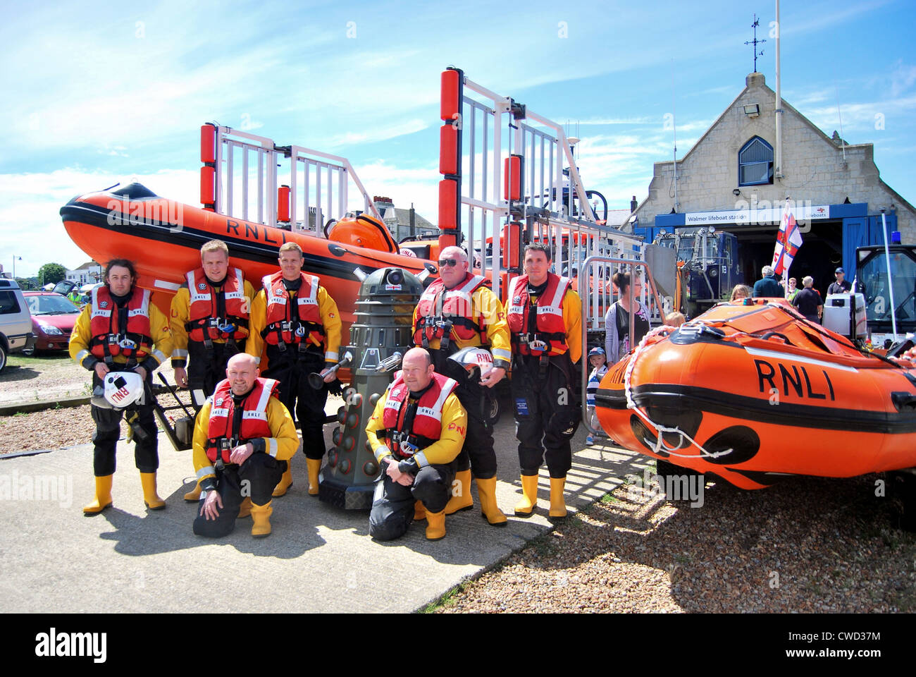 Walmer RNLI Lifeboat crew have a photograph with its latest crew member, with both of the stations lifeboats either - Stock Image