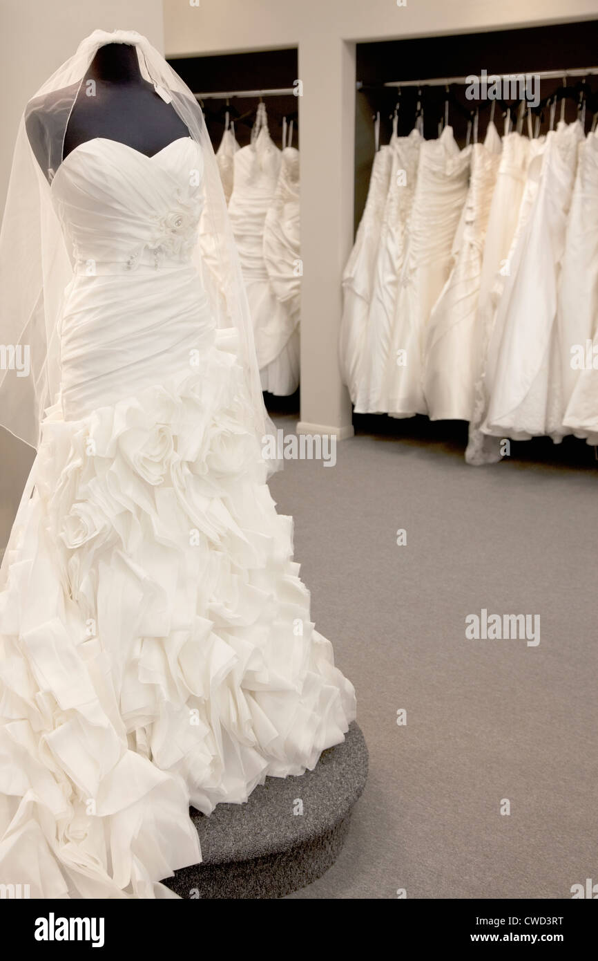 Elegant wedding dress displayed on mannequin in bridal store Stock Photo
