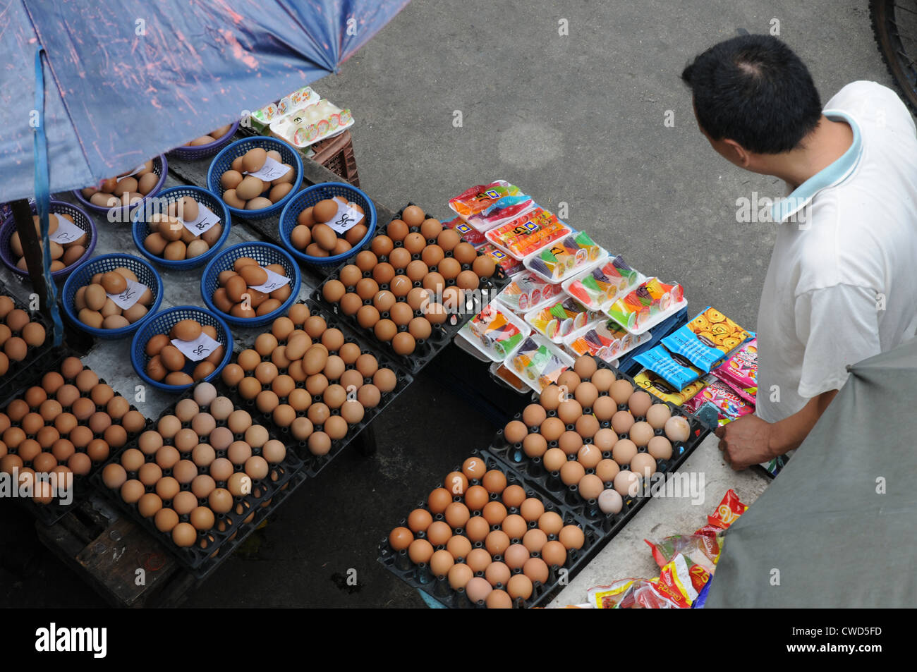 Eggs and sundry items for sale, street stall and stallholder, off Sukhumvit Road, Bangkok. Stock Photo