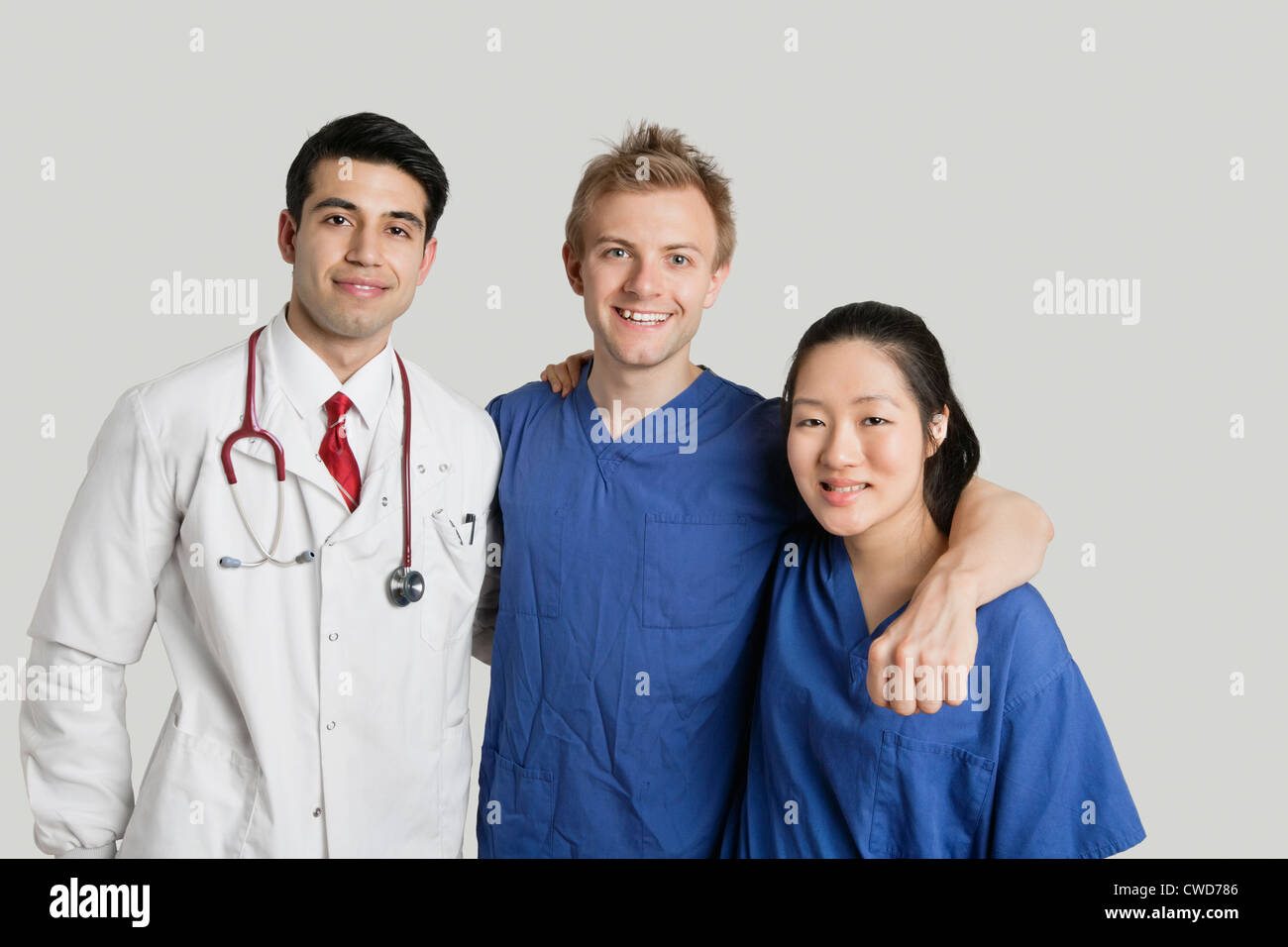 Portrait of friendly medical team standing over gray background - Stock Image