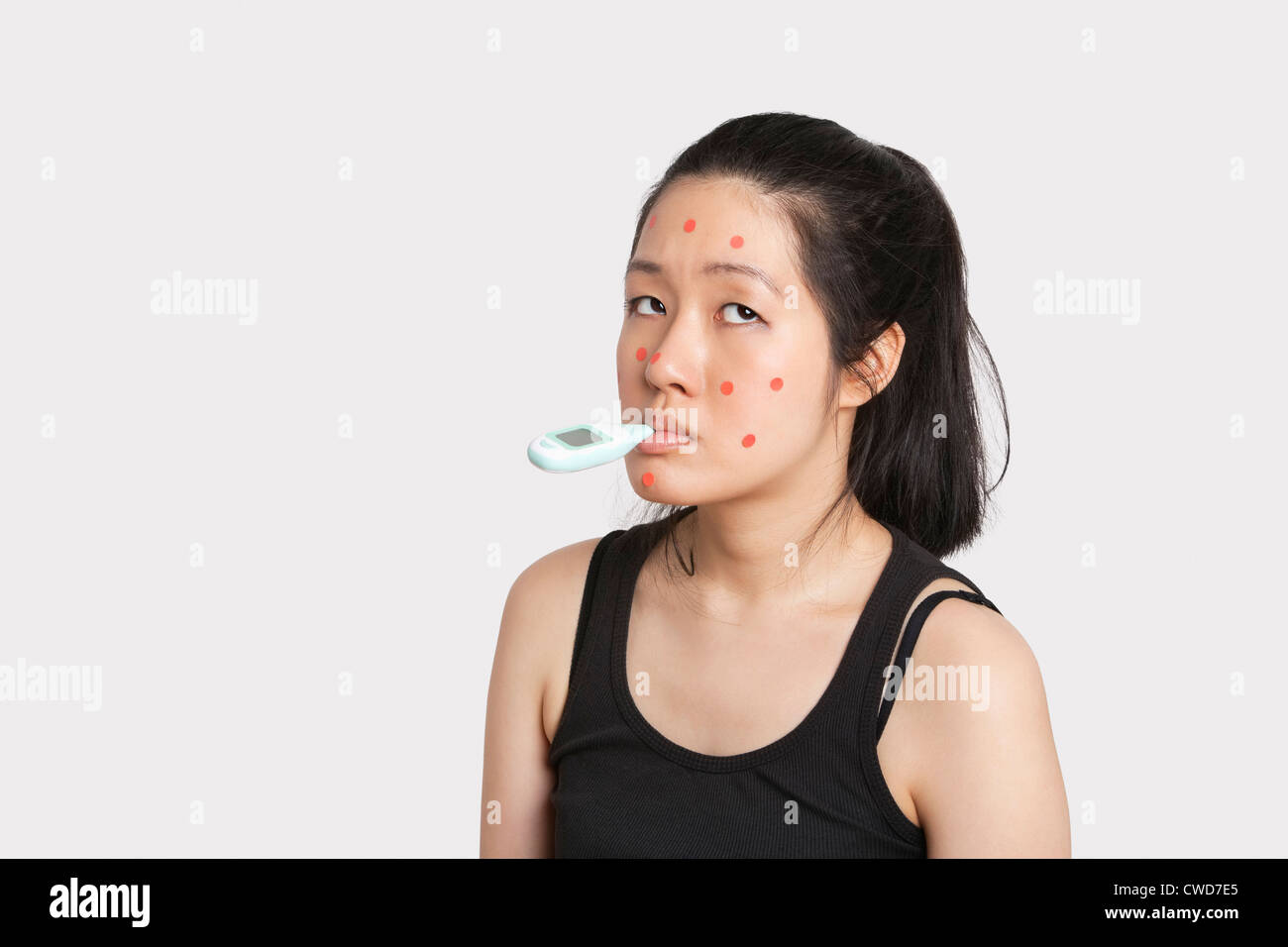 Woman with thermometer in mouth suffering from measles - Stock Image