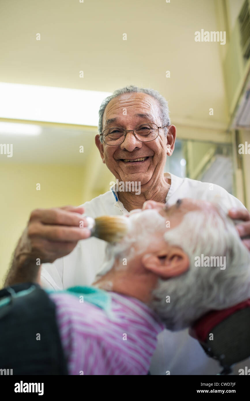 Elderly barber with shave brush applying cream to client in old style shop, smiling at camera - Stock Image