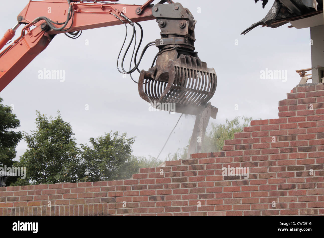 Mechanical grab demolishing old building - Stock Image