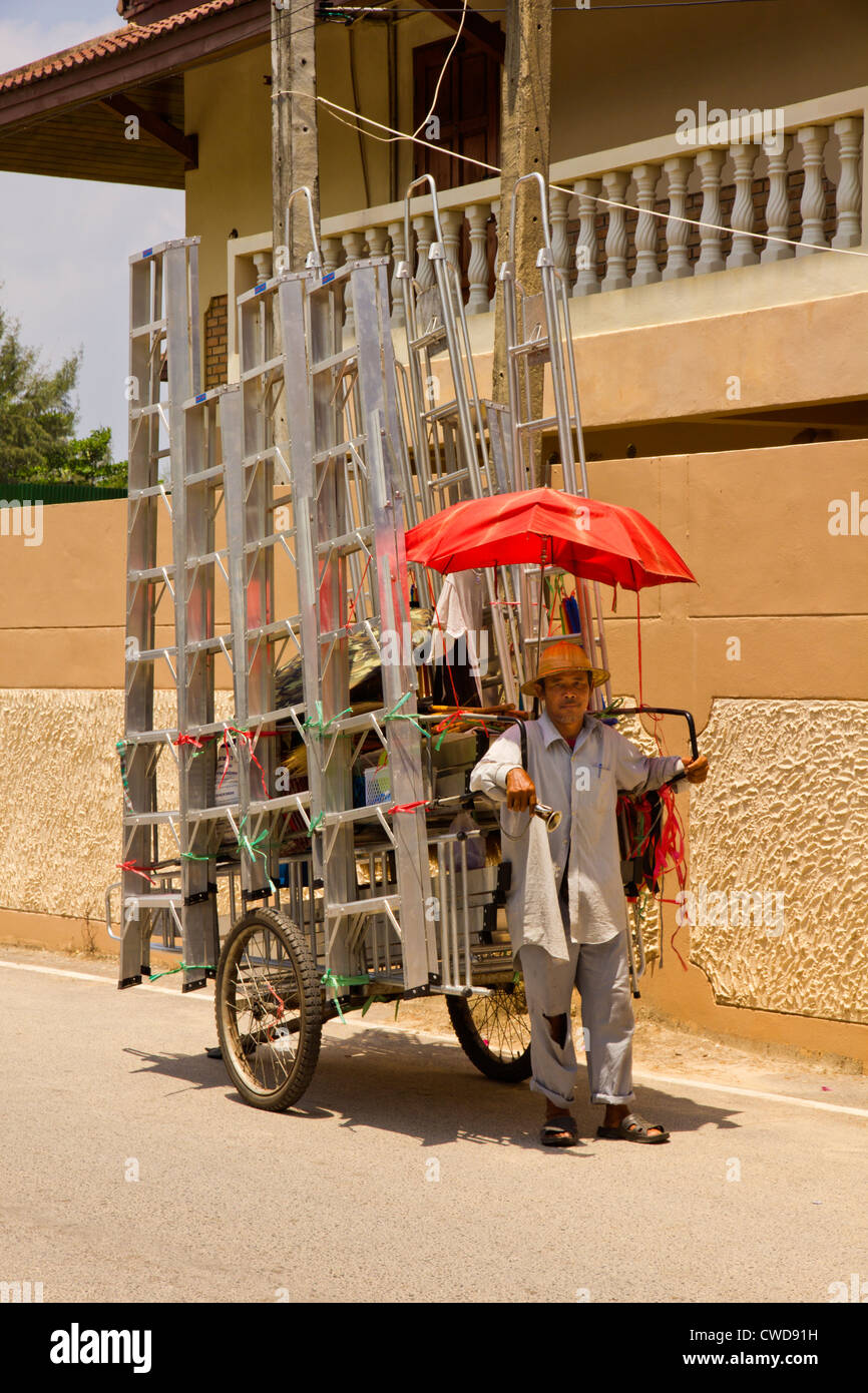 A Thai Man selling Aluminium ladders from a two wheeled cart. - Stock Image
