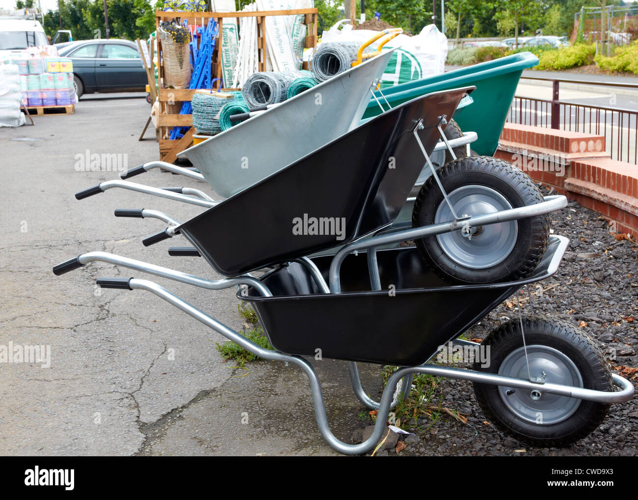 New steel wheelbarrows for sale at an agricultural merchants - Stock Image