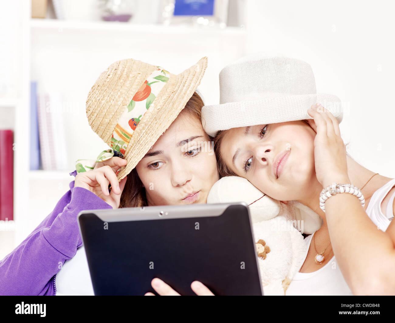 Two happy teenage girls having fun using touchpad computer - Stock Image