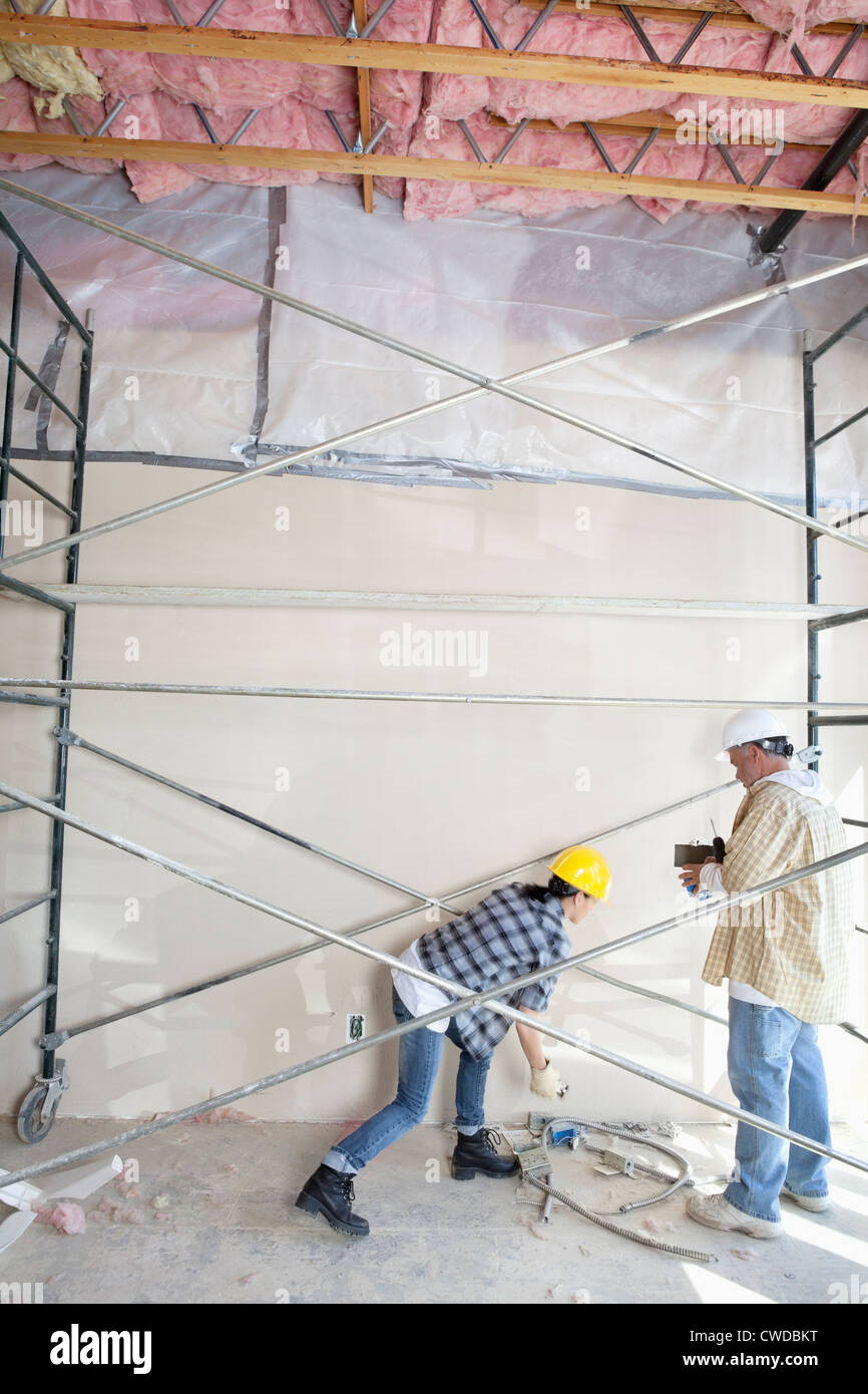 Male and female worker standing under scaffold at construction site Stock Photo
