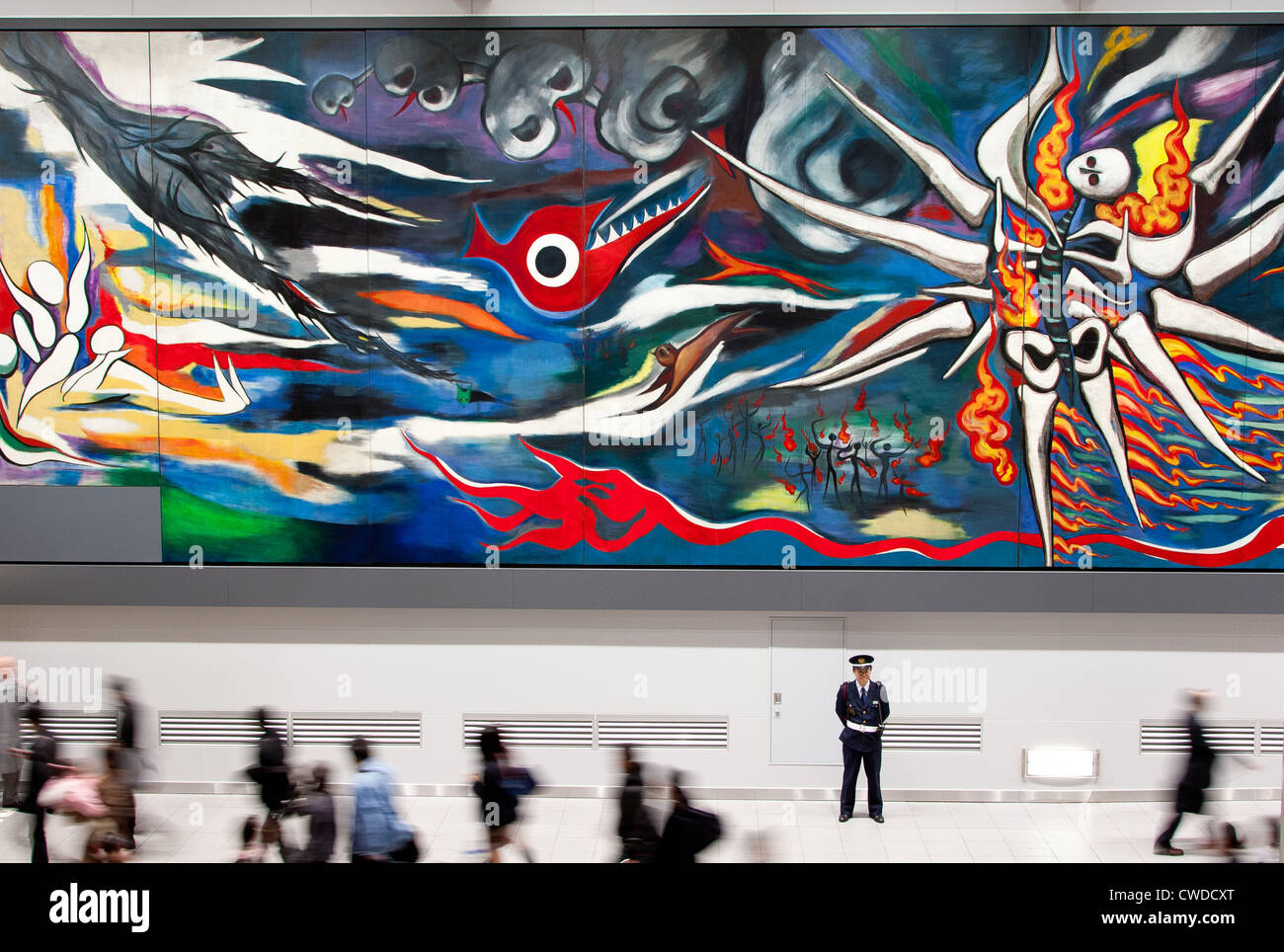 A security guard stands in front of the 30-metre-long painting called 'Myrth of Tomorrow' in Shibuya Station, - Stock Image