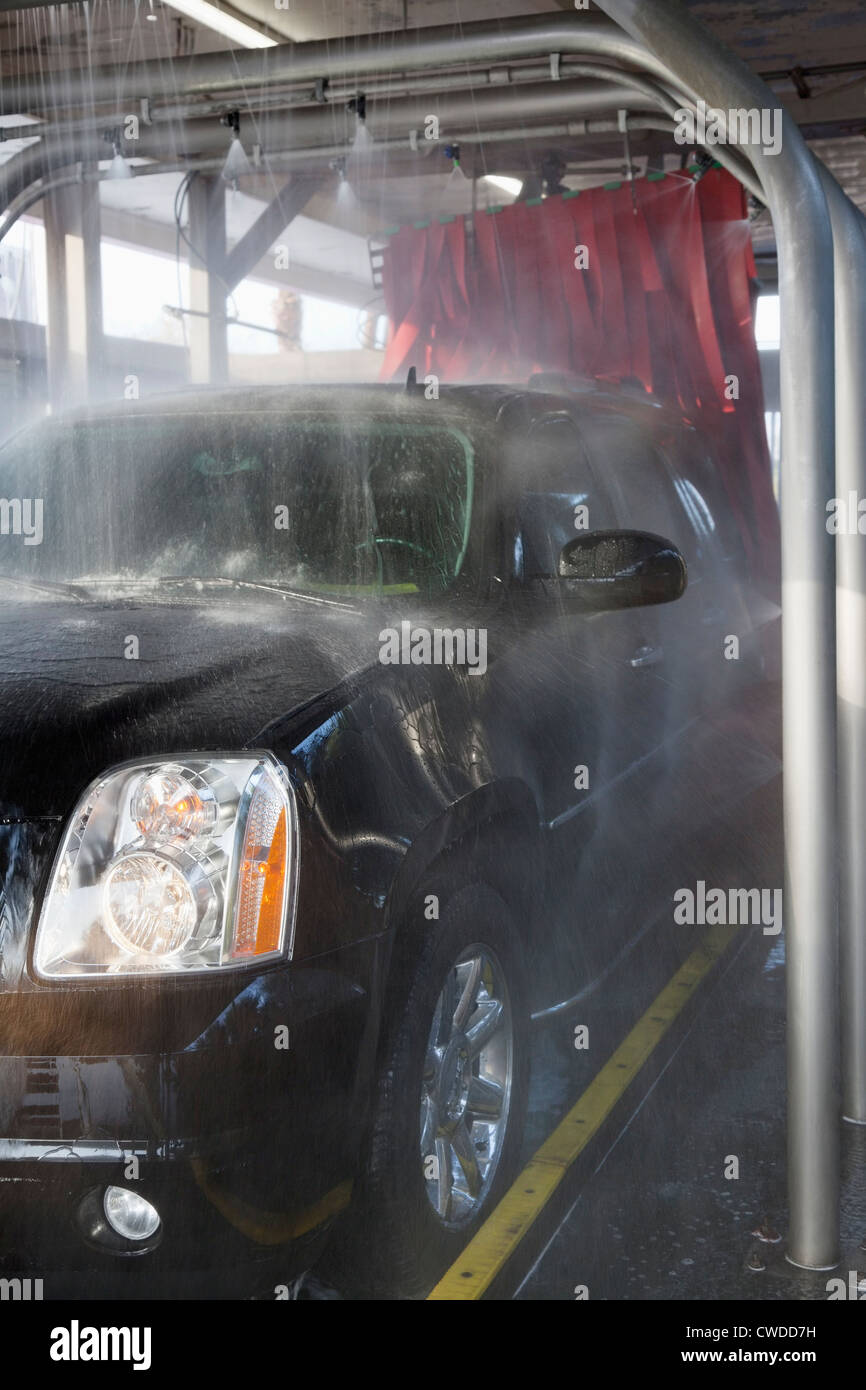 Spraying water on automobile in car wash - Stock Image