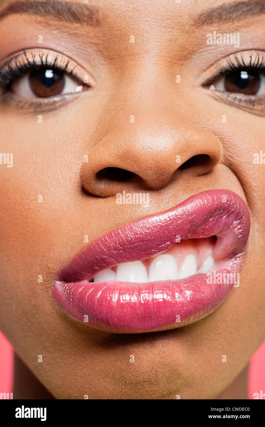 Close-up portrait of young woman with pink lips grimacing - Stock Image