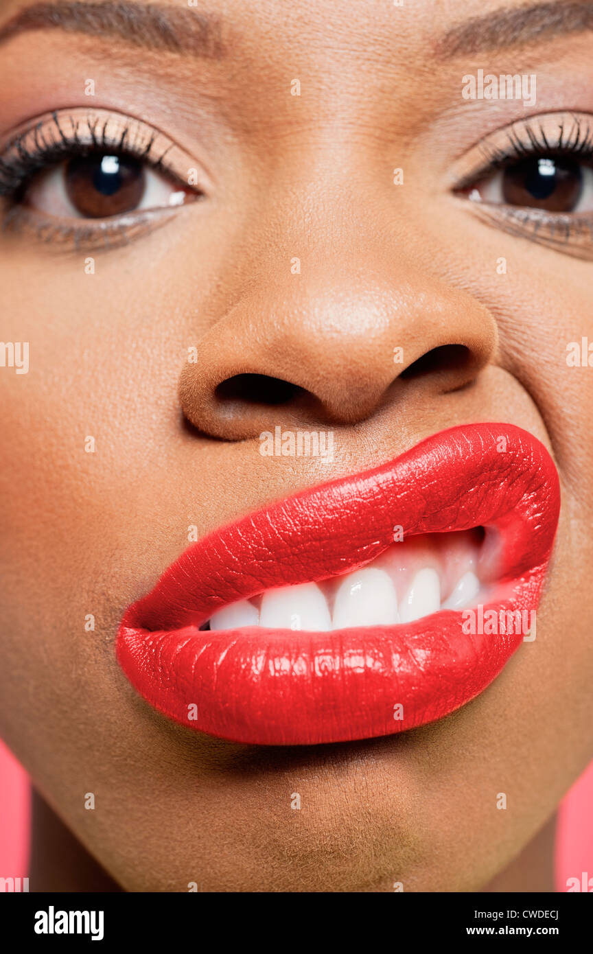 Close-up portrait of young woman with red lips grimacing - Stock Image