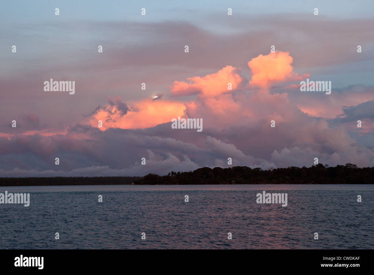 Early morning light reflects off clouds just as the moon is beginning to set. Stock Photo