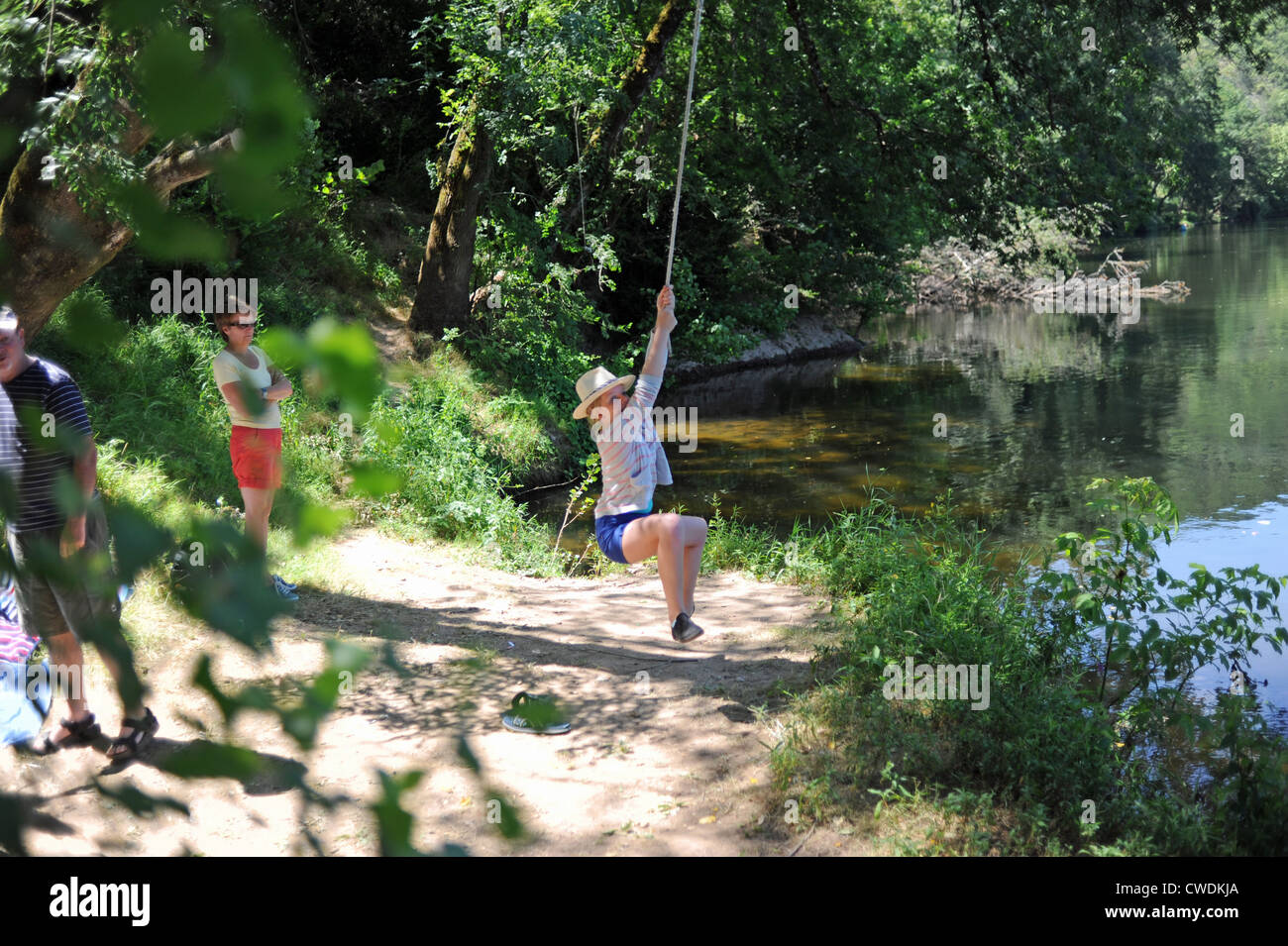 Family having fun on a rope by the river in the Lot Region of South West France Europe Stock Photo