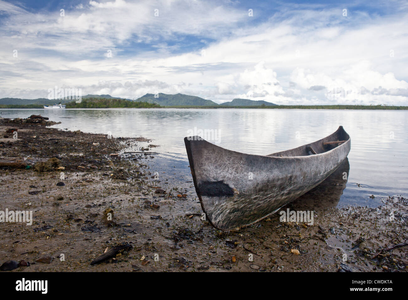 A dugout canoe is pulled up to shore near a remote village that lies in the Russell Islands, part of the Solomon - Stock Image